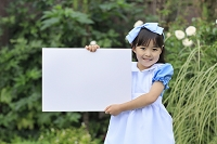 ハロウィンの仮装をしてメッセージボードを持つ女の子