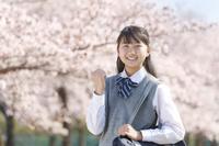 桜とガッツポーズをする女子中学生