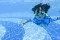 プールに潜って泳ぐ男の子