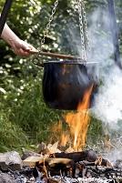 焚き火で調理される野菜スープ