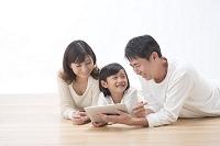 タブレットを見ている三人家族