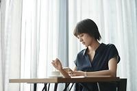 カフェでスマホを見る日本人女性