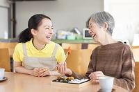 お弁当を食べるおばあちゃんと付きそう介護士の日本人女性