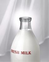 たなびくカーテンの前にある瓶に入った牛乳