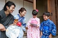 縁側で話す浴衣の日本人家族