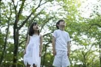 緑の中で空を仰ぐハーフの男の子と女の子