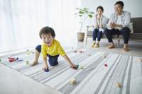 おもちゃで遊ぶ子供を見守る両親