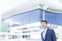 空港の前で見上げるミドル世代の日本人ビジネスマン