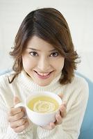 スープを飲む若い女性