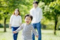 公園を走る息子を見つめる両親