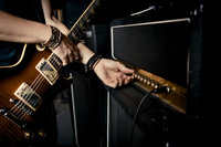 アンプのボリュームを上げるギタリスト
