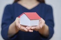 家の模型を持つ女性の手元