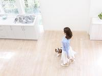 キッチンを歩く日本人女性と犬