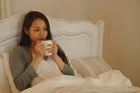 ベッドでドリンクを飲む日本人女性