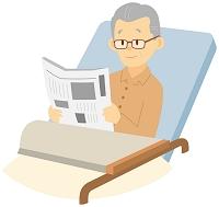 介護ベッドで新聞を読むシニア日本人男性