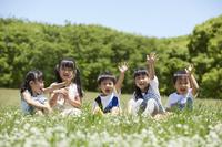 花畑で手を上げる日本人の子供達