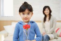 母の日に赤い花を贈る女の子