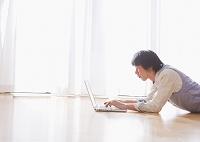 窓際でノートパソコンを操作するミドルの日本人男性