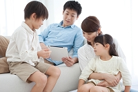 タブレットを見て話す日本人家族
