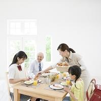 テーブルを囲み朝食をとる日本人家族