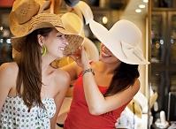 帽子店でショッピングを楽しむ外国人女性たち