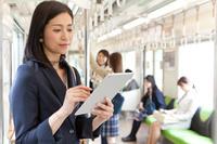 通勤電車でタブレットを見ているビジネスウーマン