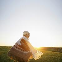 夕暮れの草原に立つ日本人女性