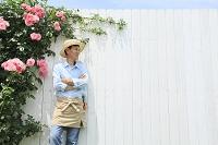 バラと白い壁の前に立つ中年日本人男性