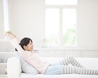 ソファに座って伸びをする日本人女性