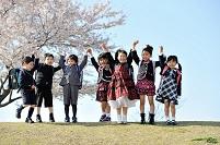 桜の咲く公園で手を繋いでる日本人の小学生