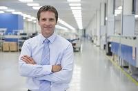 工場で腕組をする笑顔のビジネスマン