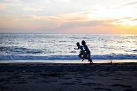 夕焼けの砂浜を走る若い男性