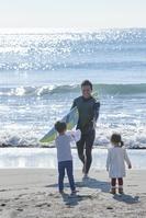 サーフボードを持って砂浜を歩く親子