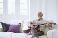 ソファでギターを弾くシニアの日本人男性