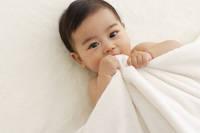 まっ白いタオルをかぶり寝転がる赤ちゃん