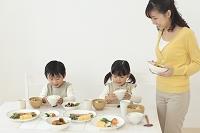 食卓に食事を運ぶ子供達とママ