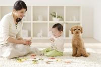 リビングで木のおもちゃで遊ぶ赤ちゃんとお母さん
