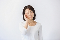 こめかみを押さえる40代日本人女性