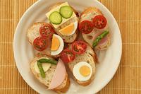 パンの上のトマトときゅうりとゆで卵で作った顔