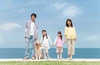 海岸で手を繋ぐ家族と犬