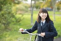 自転車を押しながら振り返る女子高校生