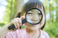 虫眼鏡を持つ日本人の女の子