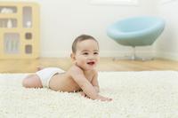 リビングに寝そべる笑顔の日本人の赤ちゃん