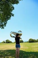 夏の公園の木陰でチューバを吹く女性