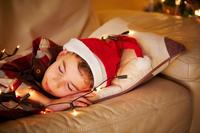 クリスマスにソファで横になる男の子