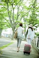 旅行カバンを持った日本人女性の後ろ姿