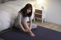 寝室でセルフマッサージをする日本人女性