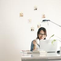 ノートパソコンを開き仕事をするビジネスウーマン
