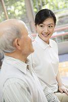 座りながら談笑するシニア男性と介護士