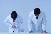 謝罪する白衣を着た日本人男女